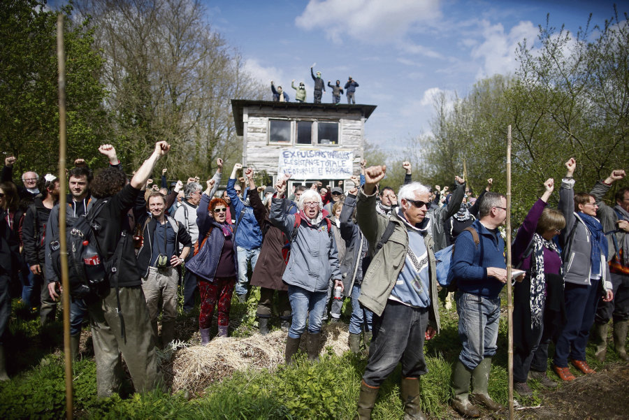 Protesters react as they gather during the evacuation operation by French gendarmes in the zoned ZAD (Deferred Development Zone) at Notre-Dame-des-Landes